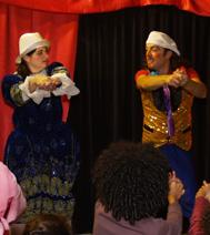 un magicien sur scène, avec les enfants dans le public