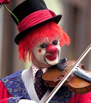 Durant le spectacle, le clown joue du violon : les enfants adorent